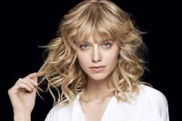 Wild waves. To play with the rock chick style, here the layers have been given a completely different look with waves. The locks form large tousled curls whereas the full fringe is slightly curved to blend in with the big waves. To create this wavy look and to give it maximum volume, the locks are wrapped around large-diameter curling tongs. They are then finished off with Beach Spray, a salt water lotion which boosts the hair's volume and texturizes it for a surefire rock chick look!