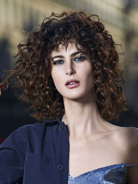 To radically transform your haircut, the hair is thickened and coated with Design Spray, a texturizing product which creates volume. It is then curled with small diameter curling tongs to form ultra-tight curls. These are then relaxed by lightly shaking your hair upside-down for sexy curls full of bounce. Finally, the whole look is held in place with a long-lasting hold hairspray.